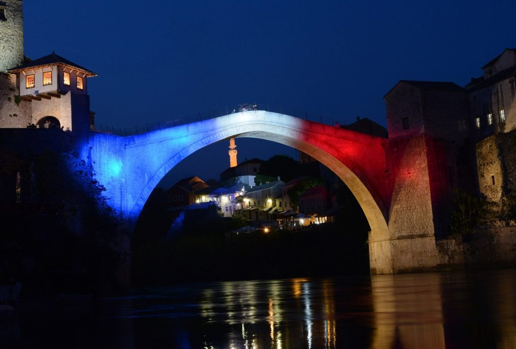 Mostar Bridge is illuminated with the colours of French flag following the massive fire