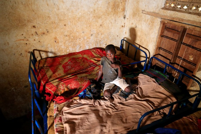 Twelve of the children sleep on metal bunk beds with thin mattresses in one small room with grime-caked walls