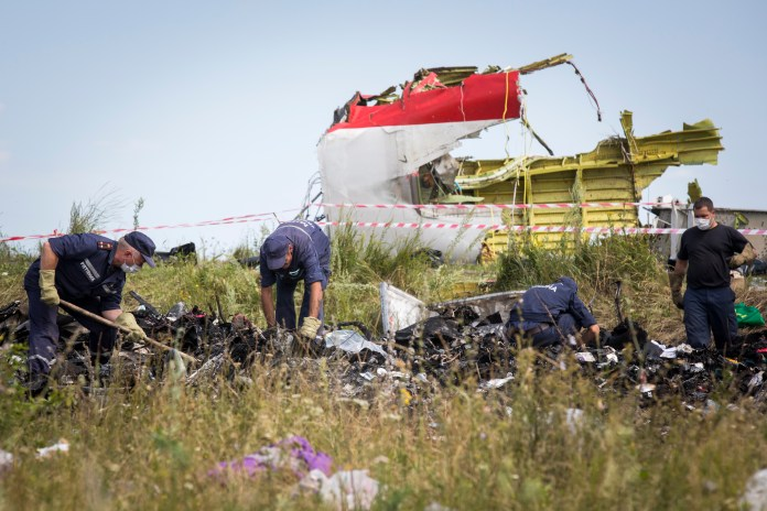 Air crash investigators inspect the crash site in a filed in Ukraine