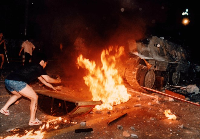 A student protester puts barricades in the path of an already burning armoured personnel carrier