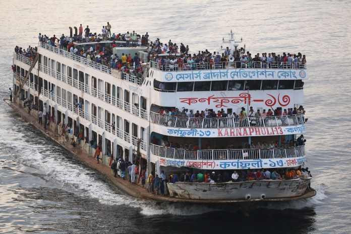 People travel home on a packed ferry for the festival which marks the end of Ramadam