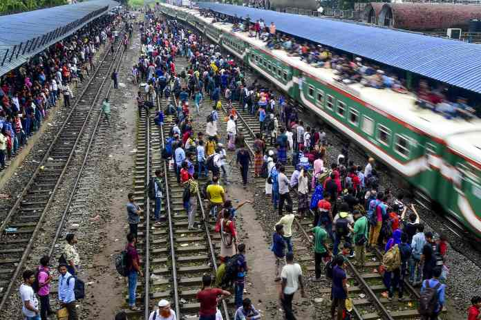 People try to leap onto a moving train as it passes through the station at Dhaka