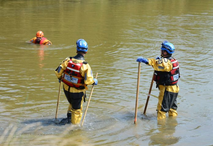 Search and Rescue personnel searching near a sluice gate in Wootton Creek