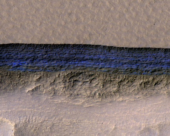 A cross-section of underground ice exposed at a steep slope on Mars. The ice appears bright blue in this enhanced image from Nasa's Mars Reconnaissance Orbiter. The scene is about 1,500ft wide