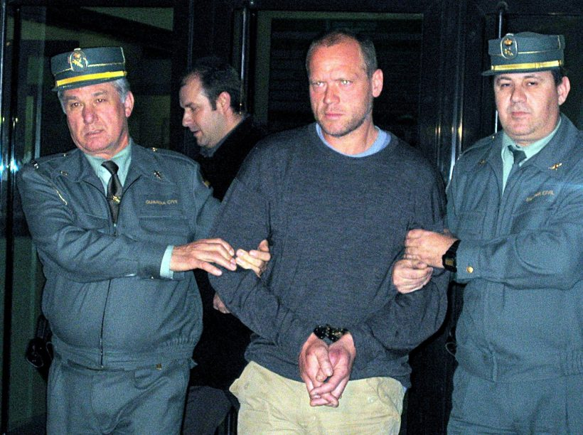 Durant led away by Spanish police after the murder in early 2004 in a village near Benidorm