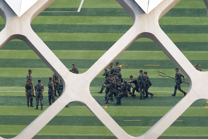 Chinese soldiers practice on the grounds of the Shenzhen Bay Sports Center