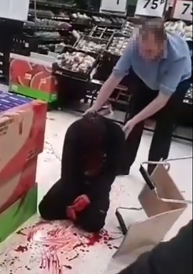 An Asda worker tries to keep him on his feet but he collapses to the floor