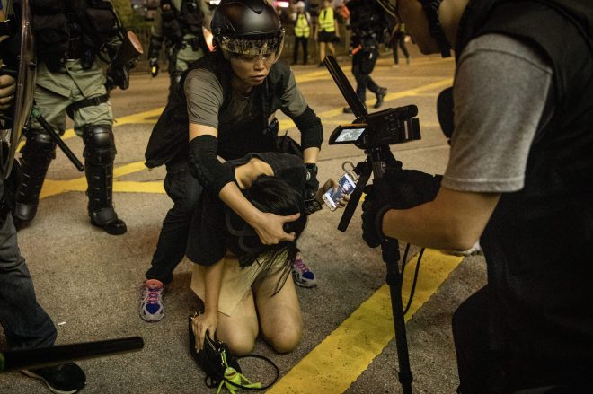 A young woman is arrested by police