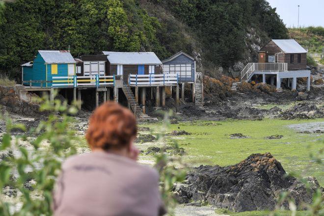 A woman looks at bungalows forbidden because of toxic green algae in the Vallais beach, near Saint-Brieuc