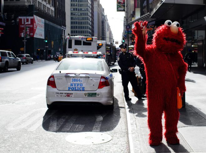 A man dressed as Elmo from Sesame Street waits to pose for pictures with tourists in New York