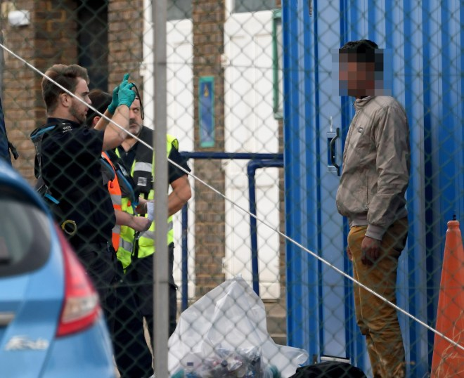 A migrant is processed by immigration officials before being taken to a detention centre
