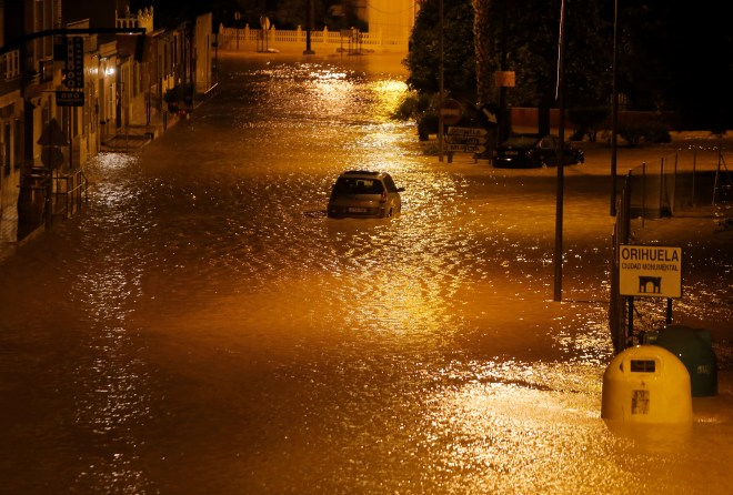 A car stuck on a flooded street as torrential rains hit Orihuela, near Murcia