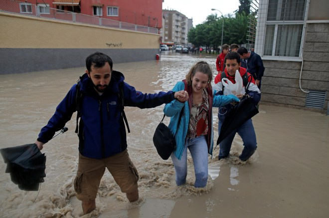 People wade through a flooded street close to the overflowing Segura river as torrential rains hit Orihuela