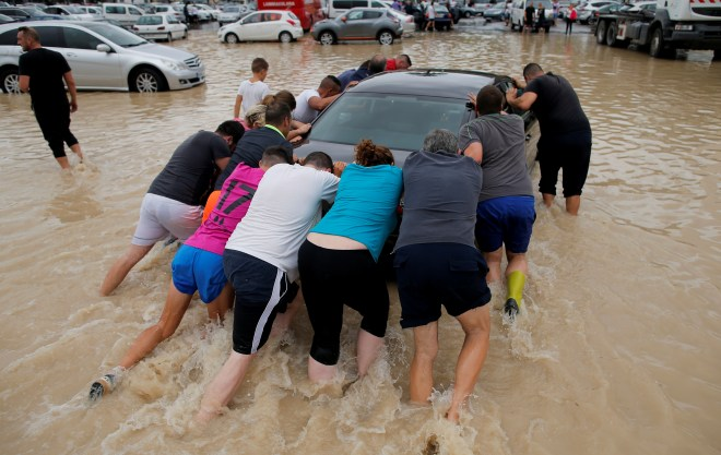 People give a helping hand to a driver stranded in floodwater in Orihuela