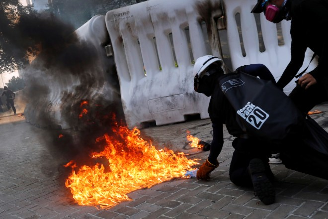 An anti-government protester prepares to throw a Molotov cocktail at riot cops