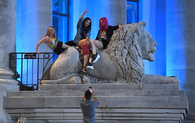 These women pose on a lion statue during the 'Big Night Out' pub crawl in Portsmouth during Freshers' Week