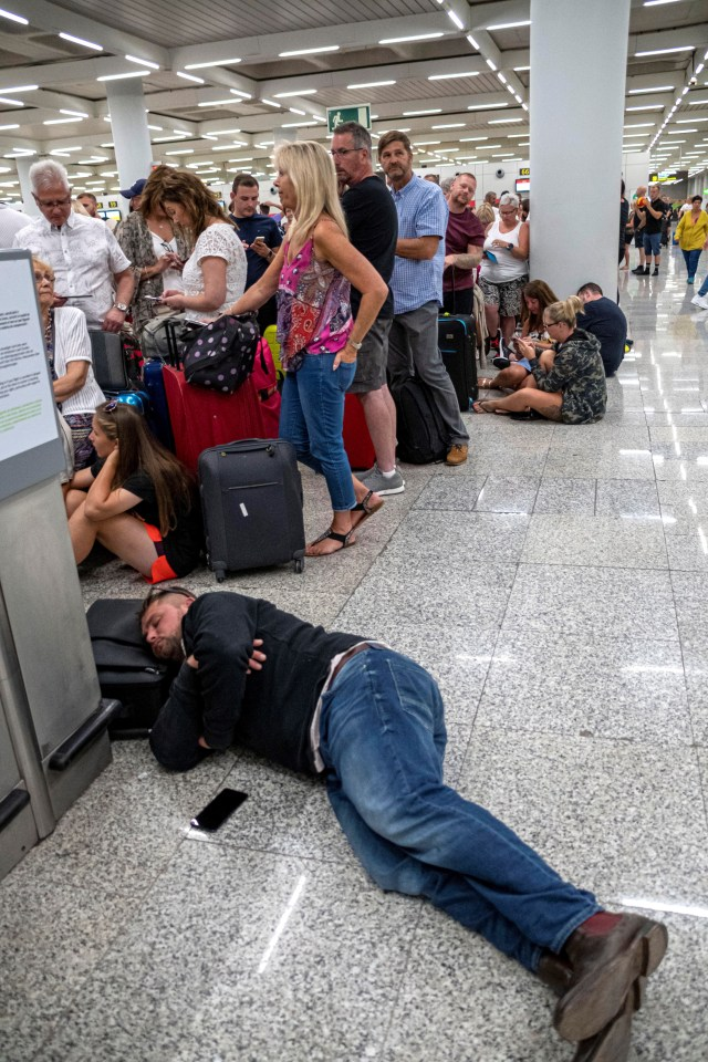 This passenger sleeps on the floor while waiting for answers at the airport in Palma de Mallorca in Majorca island