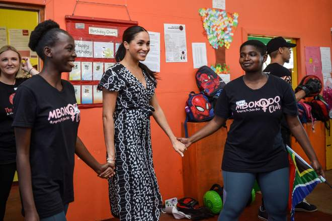 Meghan hand-in-hand with youngsters at an education workshop