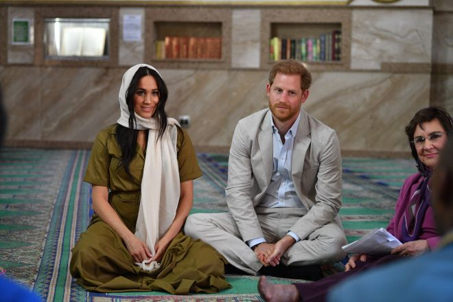 Prince Harry sits by wife Meghan Markle during a royal engagement in South Africa yesterday