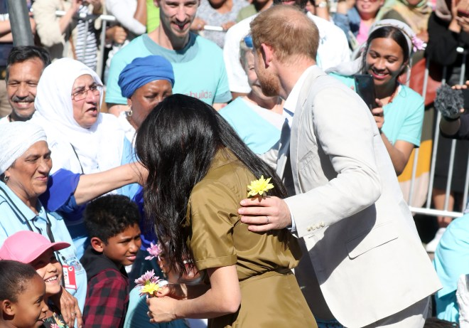 Prince Harry holds a yellow flower given to him from a fan as he puts a hand on Meghan's back