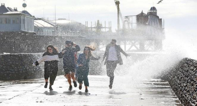 A family runs through sea spray on the South Coast as strong winds batter Brighton