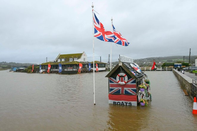A riverboat kiosk is swamped by the flood water on the river Brit at West Bay in Dorset