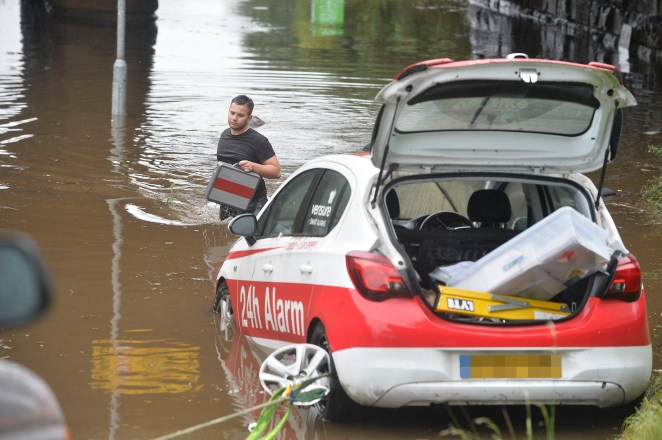 River Calder in West Yorkshire burst its banks on Sunday, forcing this driver to collect his belongings from his car.