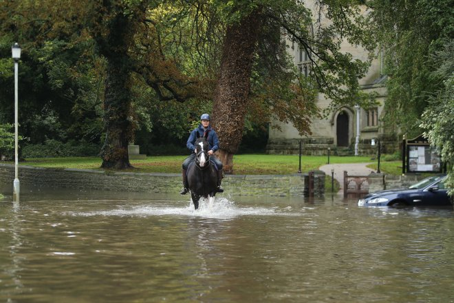 A horse rider navigates deep flood water in Colston Bassett, Notts.