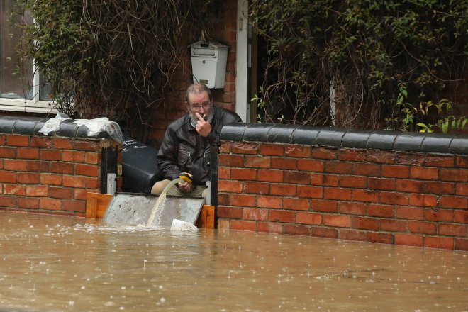 A man pumps flood water from his home after heavy rain has cut off the town of Sileby, Leicestershire