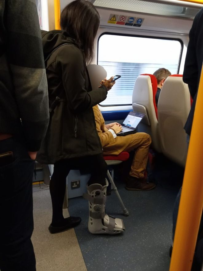 A woman on crutches can be seen standing on the train while a man sits using his laptop