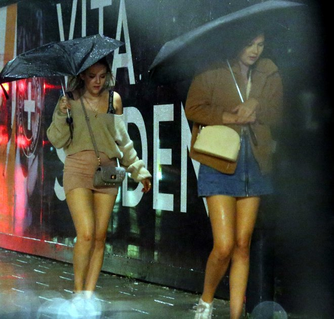 Two women try to stay dry during a storm last night in Leeds