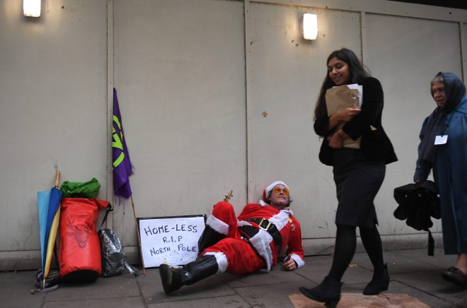 A man dressed as homeless Santa lays on the ground at Millbank