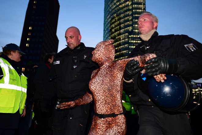A protester dressed in a leopard-print leotard is carried away by police