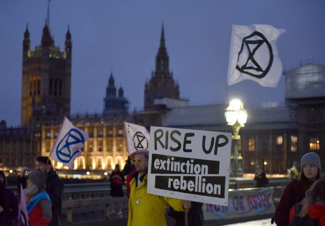 """A Protester holds up a placard saying """"Rise UP, Extinction Rebellion"""" on Westminster Bridge"""
