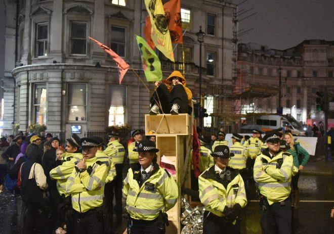Police surround a protester in Trafalgar Square