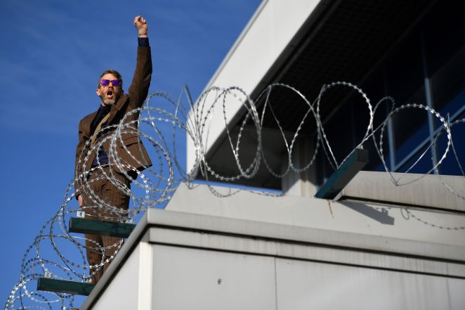 A protester on the roof above the entrance to City Airport shouted 'Rebellion!'