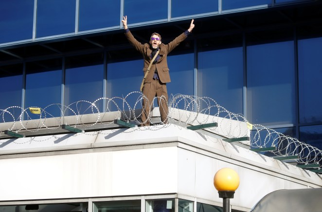 The man climbed onto the roof outside the entrance to the cheers of fellow activists
