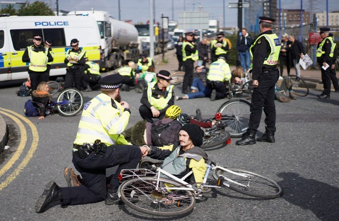 Extinction Rebellion protesters with bikes block a roundabout near City Airport