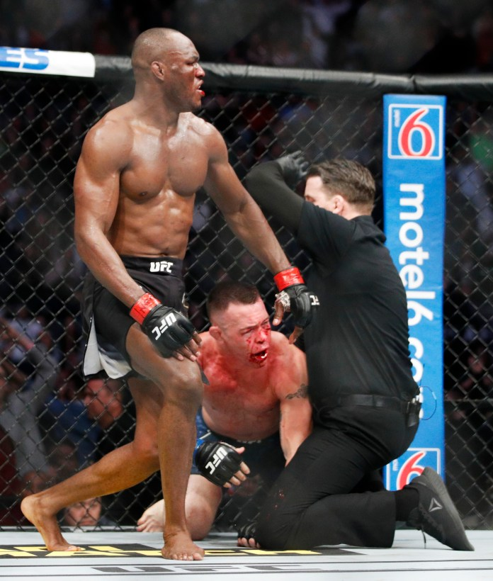 Usman celebrates as Covington is sprawled on the octagon floor with blood all over his face