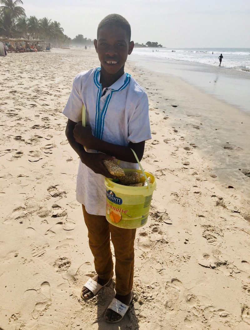 A child smiles on the beach in The Gambia, where thousands of Brits flock every year. There's no suggestion he is caught up in the child sex tourism trade