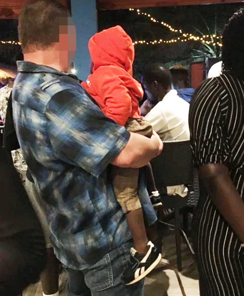 A man with a British accent holds a scared toddler in his arms