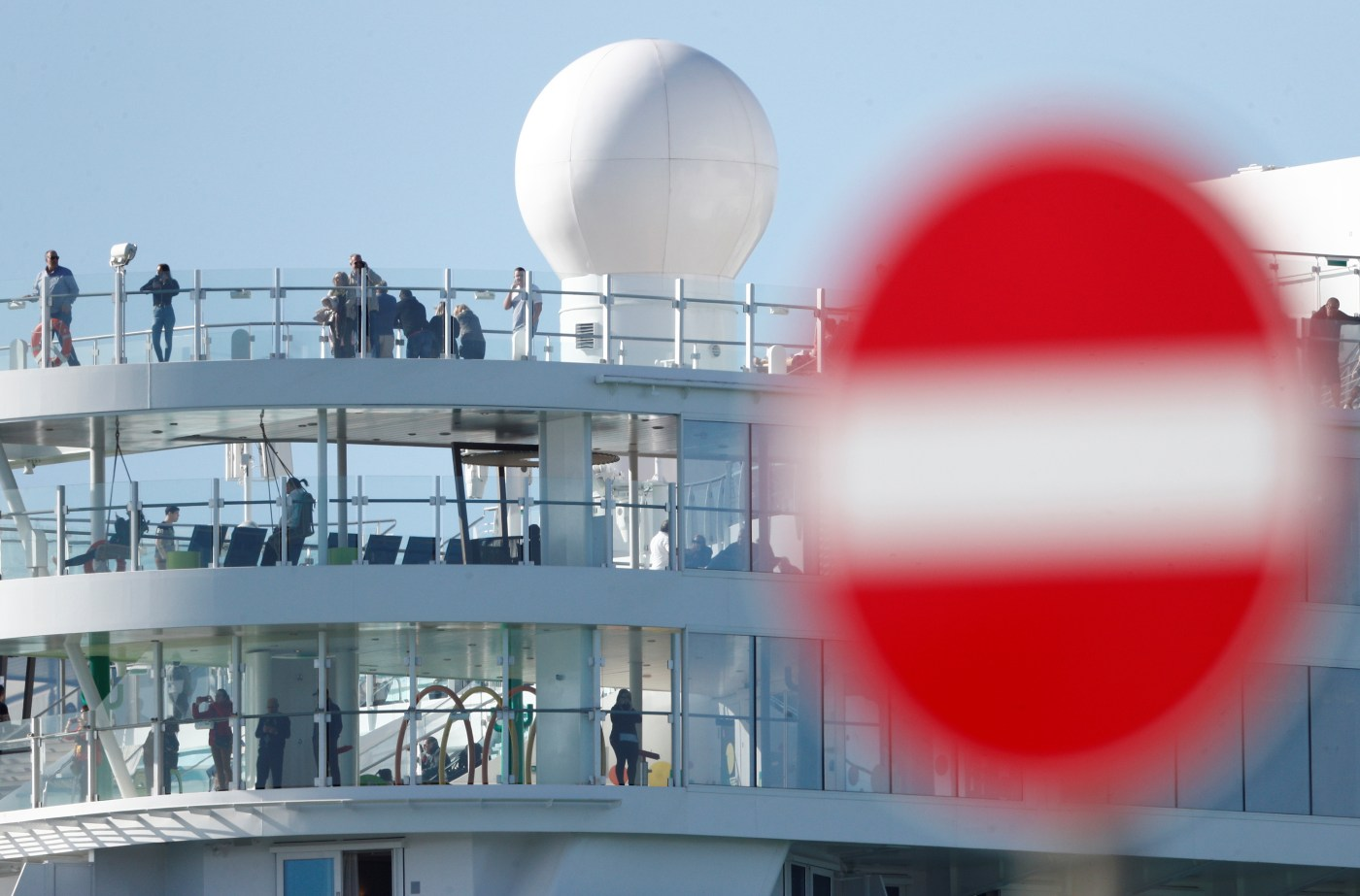 Passengers are seen on board the Costa Smeralda as it sits docked at the Italian port of Civitavecchia following a health alert