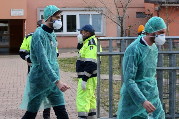 People wear protective face masks in front of a closed school in Italy, where two people have died from coronavirus