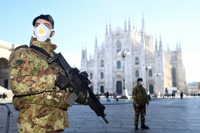 Military officers wearing face masks stand outside Duomo cathedral in Milan