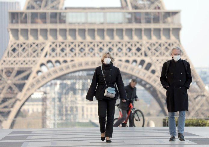 Parisians walk past Eiffel Tower last month before ban