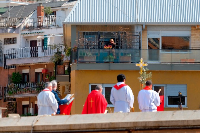 Yesterday a priest holds a Palm Sunday mass on a roof in Rome