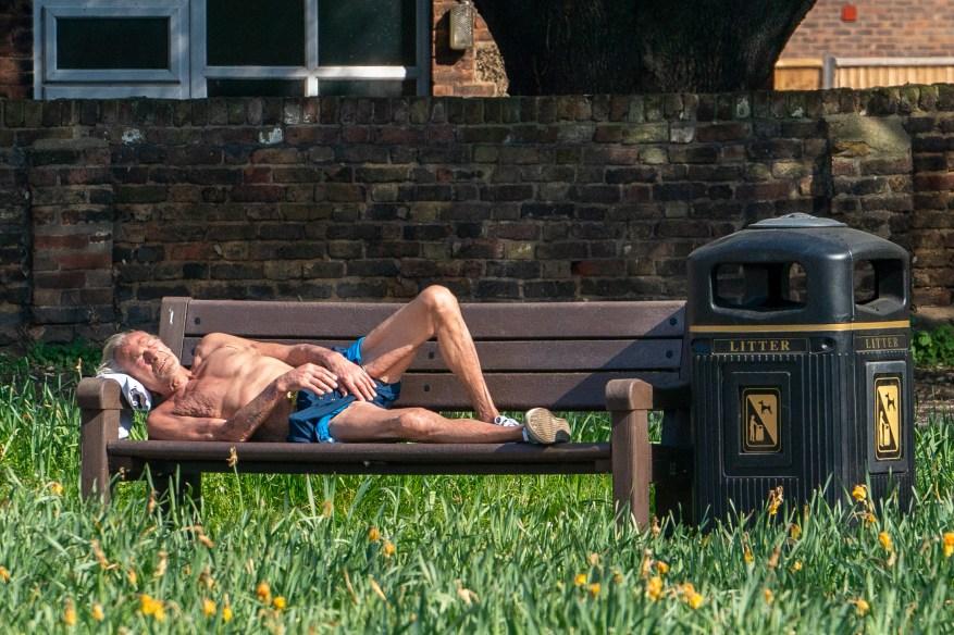 A pesar de las claras instrucciones del Gobierno de permanecer en el interior, este hombre toma el sol en un banco del parque en Thurrock, Essex.