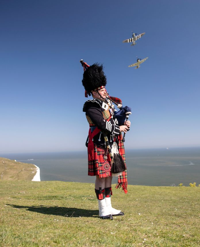 Major Andy Reid of the Scots Guards plays his pipe on the cliffs of Dover, Kent, as two Spitfires from the Battle of Britain memorial flight fly over