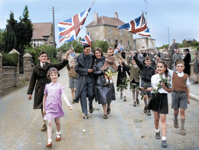 Children wave Union Jack flags and carry flowers as radiant soldier returns home to Oreston, South Devon