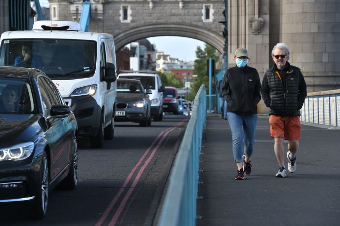 Pedestrians pass heavy traffic as they walk over Tower Bridge in London